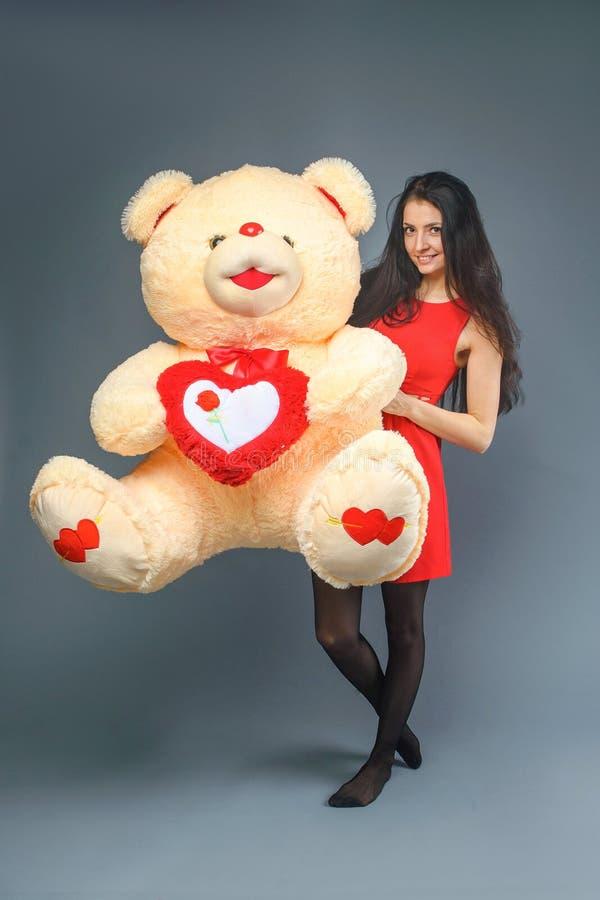 Junges schönes Mädchen im roten Kleid mit dem glücklichen Lächeln des großen Spielzeugs des Teddybären weichen und dem Spielen au stockfotografie
