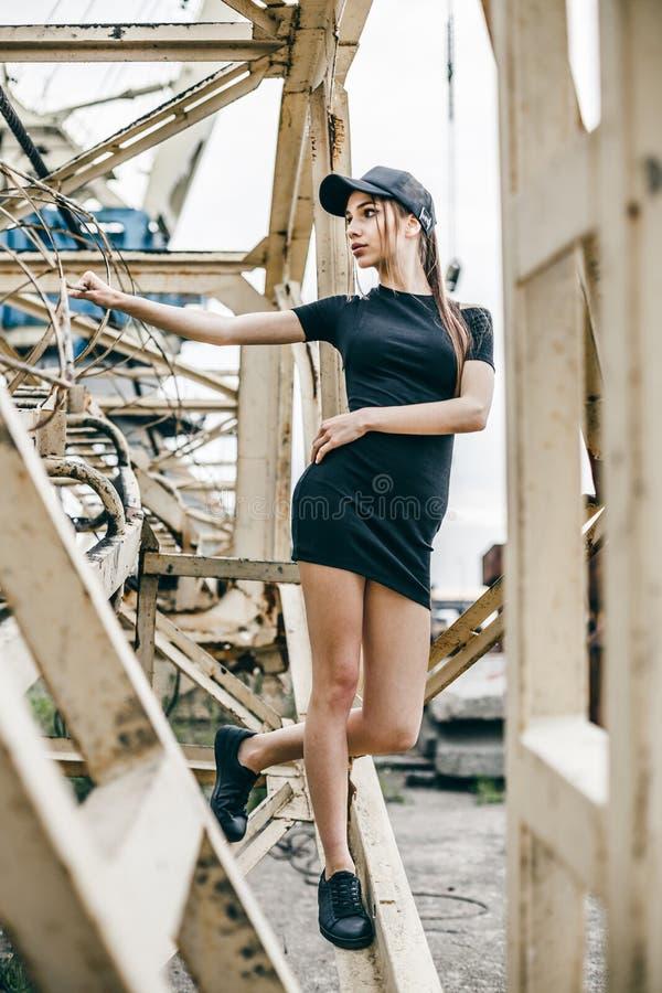 Junges schönes Mädchen im schwarzen Kleid und in der Kappe, werfend nahe Metallwand auf lizenzfreies stockbild