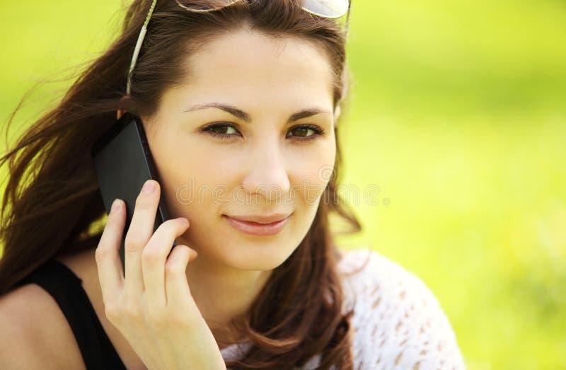 Junges schönes Mädchen im Stadtpark spricht durch bewegliches Phon lizenzfreies stockbild