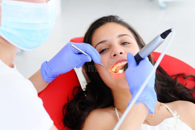 Junges schönes Mädchen im zahnmedizinischen Büro Der Zahnarzt der Kinder überprüft Zähne zu einem Kind lizenzfreie stockbilder