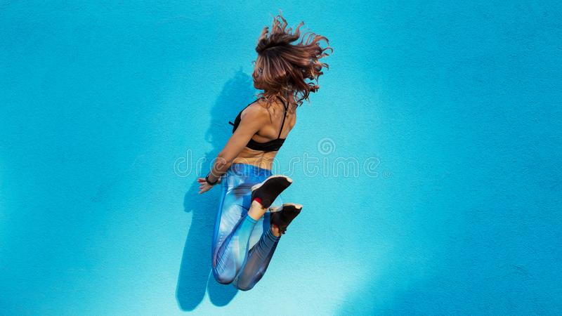 Junges schönes Mädchen mit dem gelockten Haar, das auf blauen Hintergrund springt lizenzfreie stockfotografie