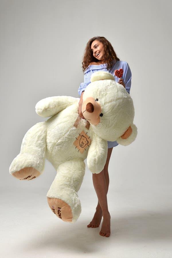 Junges schönes Mädchen mit dem glücklichen Lächeln des großen Spielzeugs des Teddybären weichen lizenzfreie stockbilder