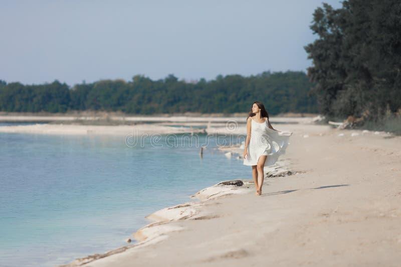 Junges schönes Mädchen mit dem langen Haar in einem weißen Kleid durch den See lizenzfreie stockfotos