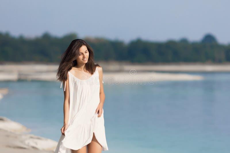 Junges schönes Mädchen mit dem langen Haar in einem weißen Kleid durch den See stockbild
