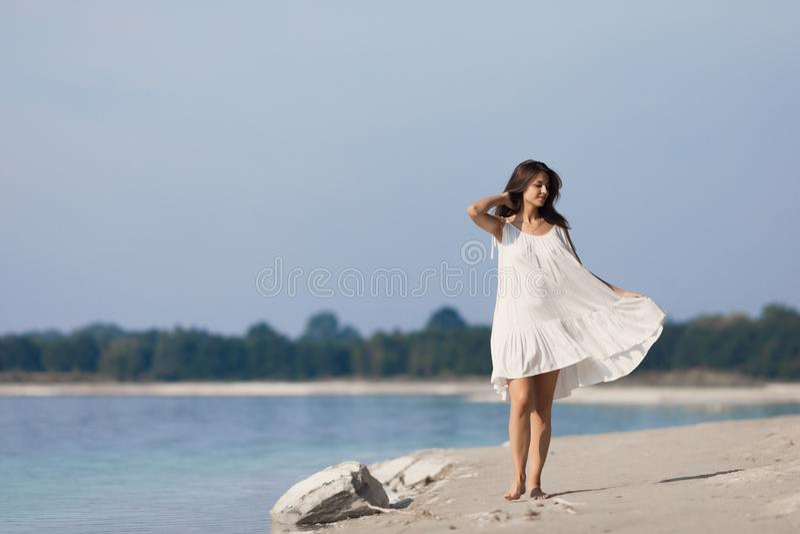 Junges schönes Mädchen mit dem langen Haar in einem weißen Kleid durch den See lizenzfreies stockfoto