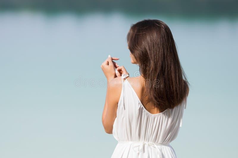 Junges schönes Mädchen mit dem langen Haar in einem weißen Kleid durch den See lizenzfreies stockbild