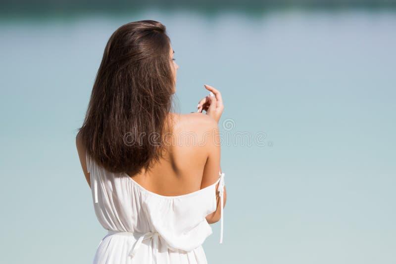 Junges schönes Mädchen mit dem langen Haar in einem weißen Kleid durch den See stockfotografie