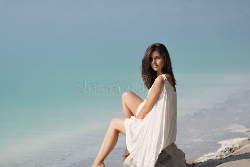 Junges schönes Mädchen mit dem langen Haar in einem weißen Kleid durch den See stockbilder