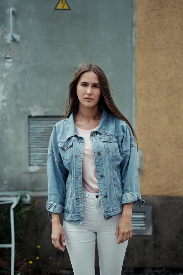 Junges schönes Mädchen mit dem langen Haar in einer T-Shirt und Denimjacke auf dem Hintergrund der Weinlesebetonmauer lizenzfreie stockfotografie