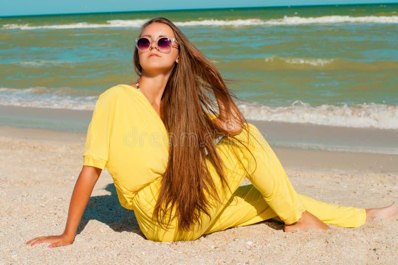 Junges schönes Mädchen mit dem langen Haar im Badeanzug am Strand lizenzfreies stockbild