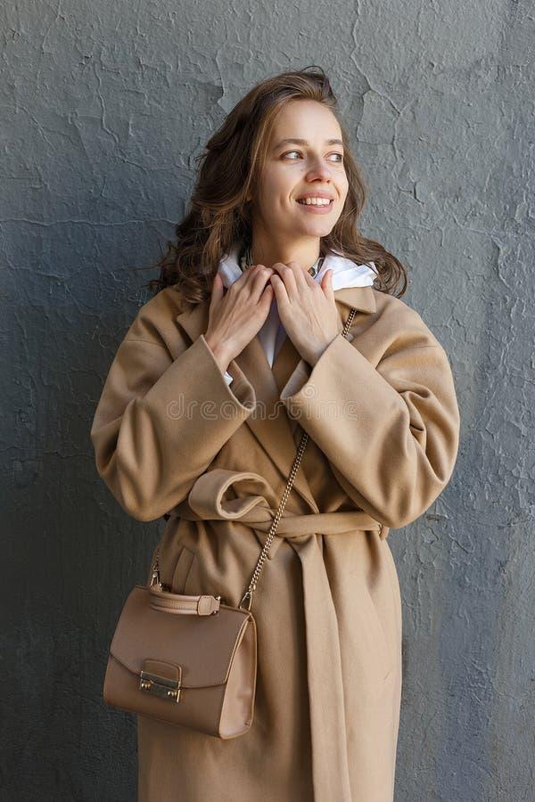 Junges schönes Mädchen mit dem langen Haar im beige Mantel an einem sonnigen Tag, der gegen ein Wandlächeln steht Stra?en-Art-Por lizenzfreies stockbild