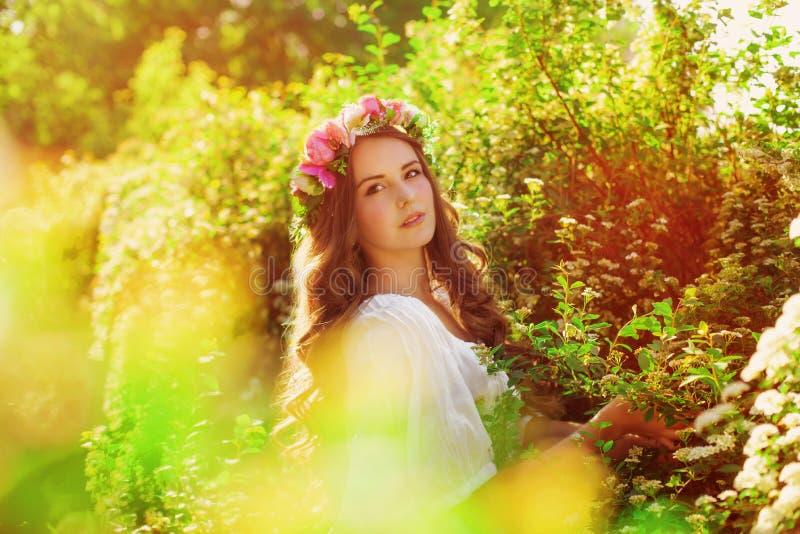 Junges schönes Mädchen mit dem langen Haar im Blumenkranz im Frühjahr stockbilder