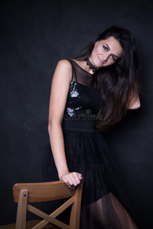 Junges schönes Mädchen mit dem langen Haar im schwarzen Kleid stockfotos