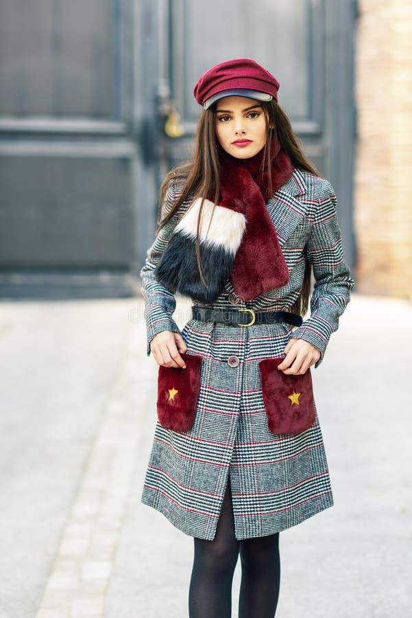 Junges schönes Mädchen mit dem sehr langen Haar, das tragenden Wintermantel der Kamera betrachtet stockfotos