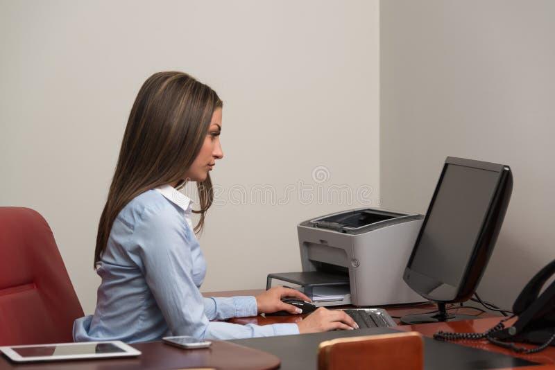 Junges schönes Mädchen mit einem Computer im Büro lizenzfreie stockfotografie