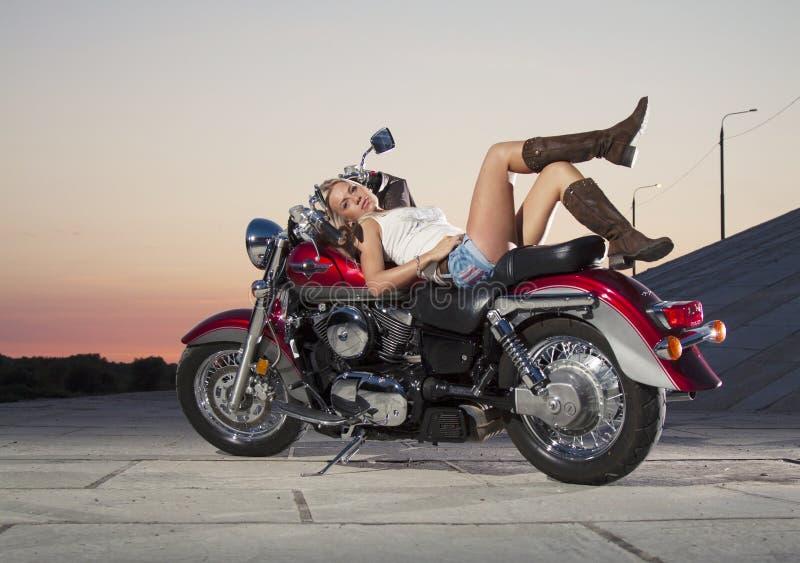 Junges schönes Mädchen mit einem Motorrad lizenzfreies stockbild