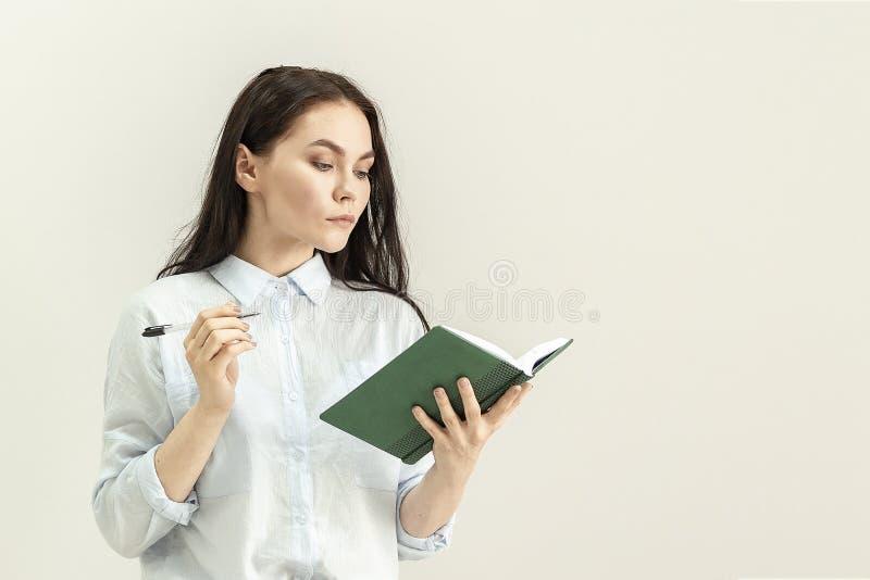 Junges schönes Mädchen mit einem Tagebuch, einem Notizbuch und einem Stift in ihren Händen stockfotografie