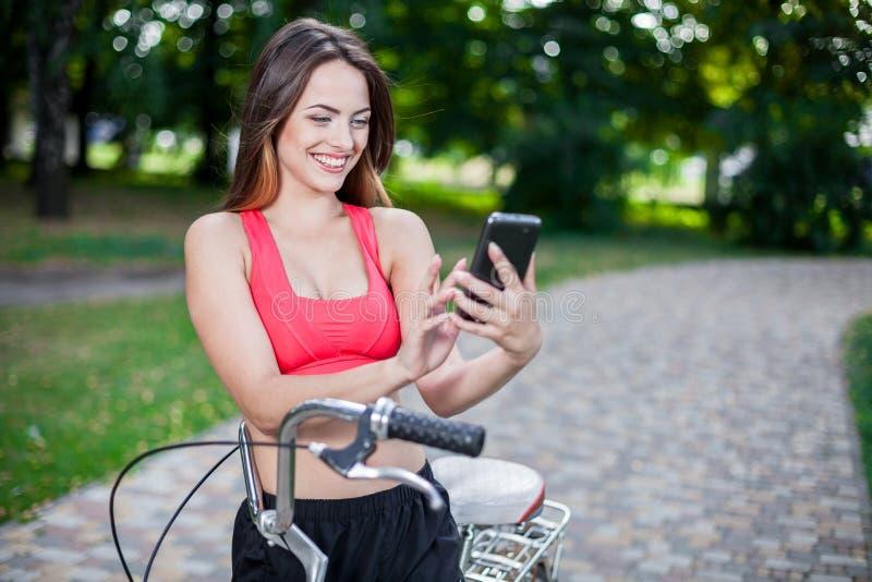 Junges schönes Mädchen mit Fahrrad lizenzfreie stockbilder