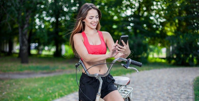 Junges schönes Mädchen mit Fahrrad stockfotografie