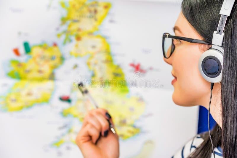 Junges sch?nes M?dchen mit Kopfh?rern und Karte von England stockbild