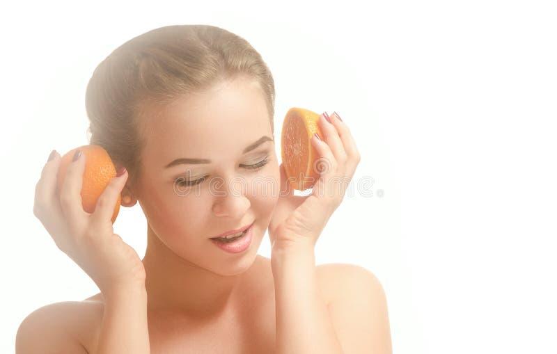 Junges schönes Mädchen mit zwei Hälften der Orange stockfoto