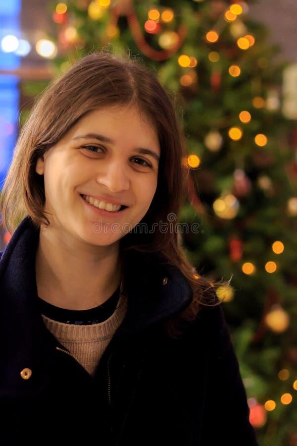 Junges schönes Mädchen nahe einem Weihnachtsbaum lizenzfreies stockbild