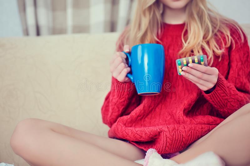 Junges schönes Mädchen oder Frau nehmen eine Pille oder eine Tablette mit einem Glas Wasser zu Hause stockbild