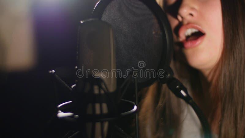Junges schönes Mädchen singt Junger Sänger, der in ein Mikrofon singt Porträt nah oben vom Sänger lizenzfreies stockbild