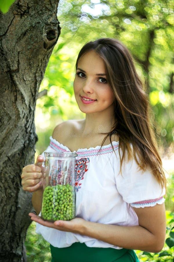 Junges schönes Mädchen steht mit einem Pitcher grünen Erbsen nahe dem Baum lizenzfreies stockbild