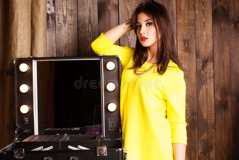 Junges schönes Mädchen visagist nahe kosmetischer Tabelle lizenzfreie stockfotografie