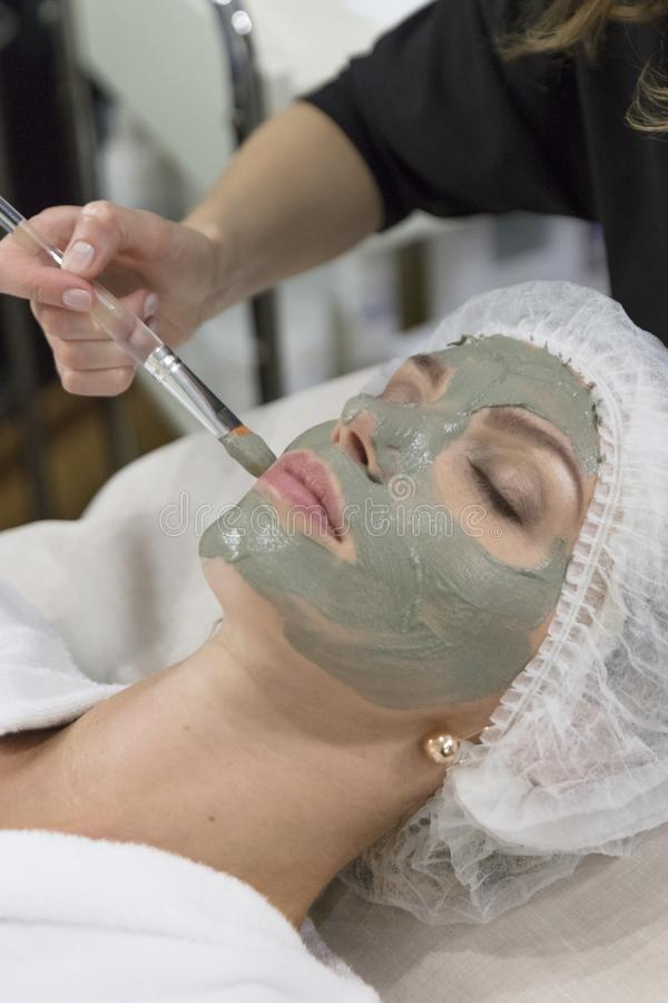 Junges schönes Mädchen, welches die Haut anhebt Gesichtsmaske im Badekurortschönheitssalon - zuhause empfängt stockbild