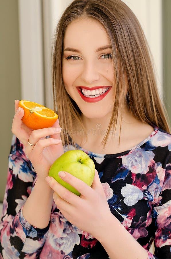 Junges schönes Mädchennahaufnahmeporträt mit orange Frucht, rotem Lippenstift und perfektem Make-up lizenzfreie stockfotografie