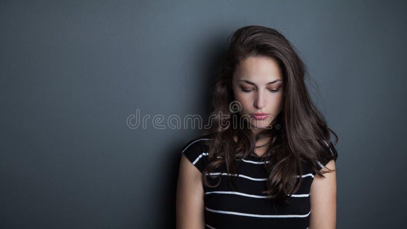Junges schönes nachdenkliches Frauenporträtstudio lizenzfreie stockfotografie