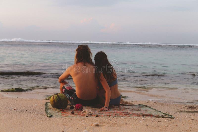 Junges schönes Paar trifft sunruse im Ozean Bali stockfotos
