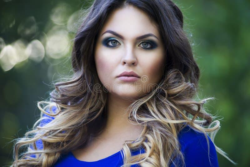Junges schönes plus Größenmodell im blauen Kleid draußen, in der überzeugten Frau auf Natur, im Berufsmake-up und in der Frisur,  lizenzfreie stockfotografie
