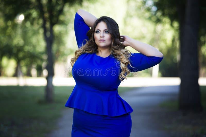 Junges schönes plus Größenmodell im blauen Kleid draußen, xxl Frau auf Natur lizenzfreie stockfotografie