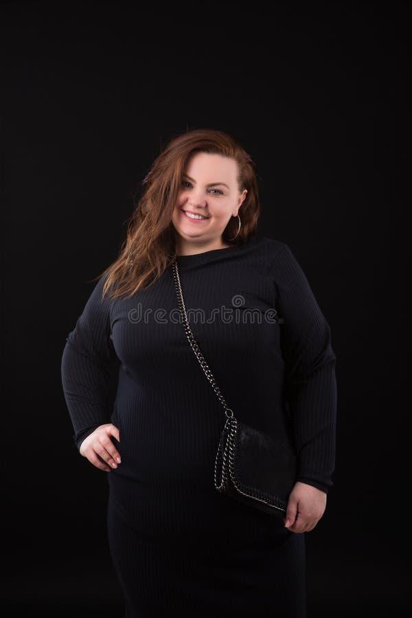 Junges schönes Plusgrößenmodell im zufälligen schwarzen Kleid, in xxl Frau auf schwarzem Hintergrund, im Berufsmake-up und in der stockfotografie