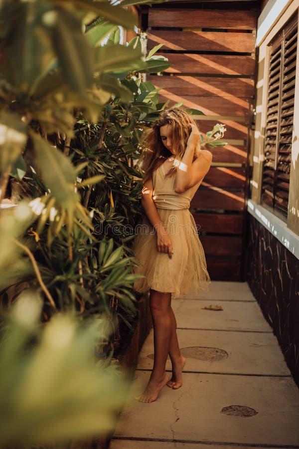 Junges schönes reiches Mädchen im gelben Kleid, das an der Palme aufwirft stockfotografie