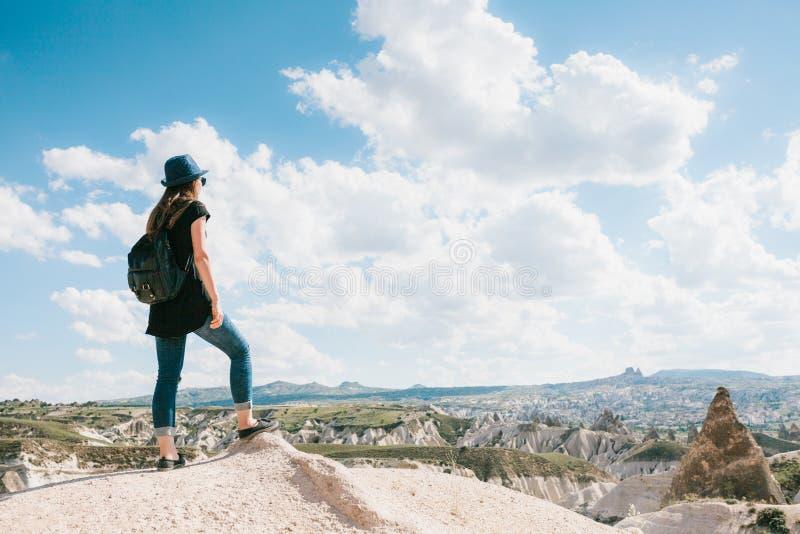 Junges schönes Reisemädchen mit einem Rucksack auf einen Hügel in Cappadocia, die Türkei Reise, Erfolg, Freiheit stockfotografie