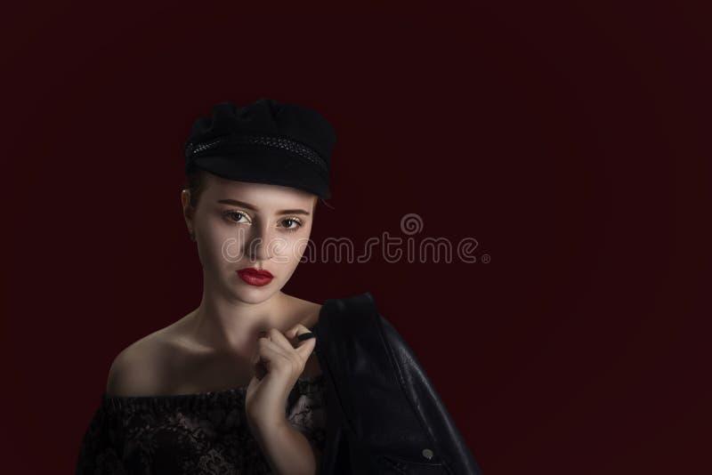 Junges schönes rothaariges Mädchen in der schwarzen Kappe mit Lederjacke stockfotografie