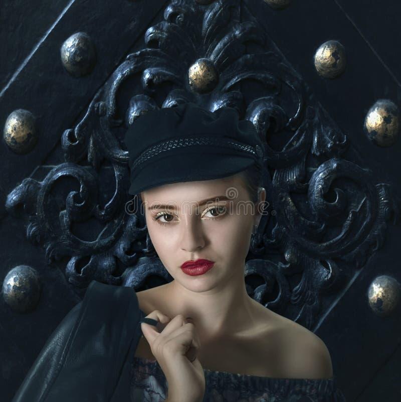 Junges schönes rothaariges Mädchen in der schwarzen Kappe mit Lederjacke lizenzfreies stockfoto
