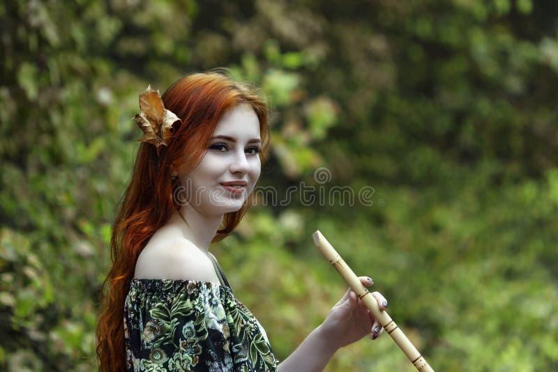 Junges schönes rothaariges Mädchen im Bild einer Elfe, die a spielt stockfoto
