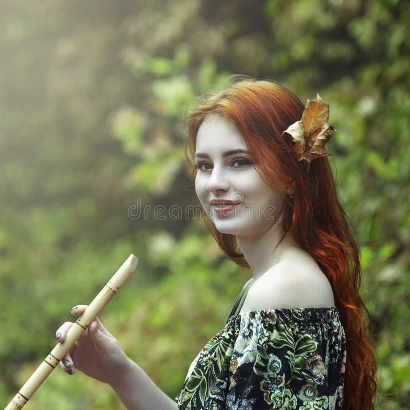 Junges schönes rothaariges Mädchen im Bild einer Elfe, die a spielt lizenzfreies stockbild
