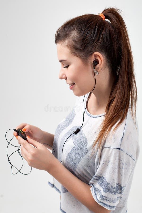 Junges schönes sportliches Mädchen hört lizenzfreie stockfotografie