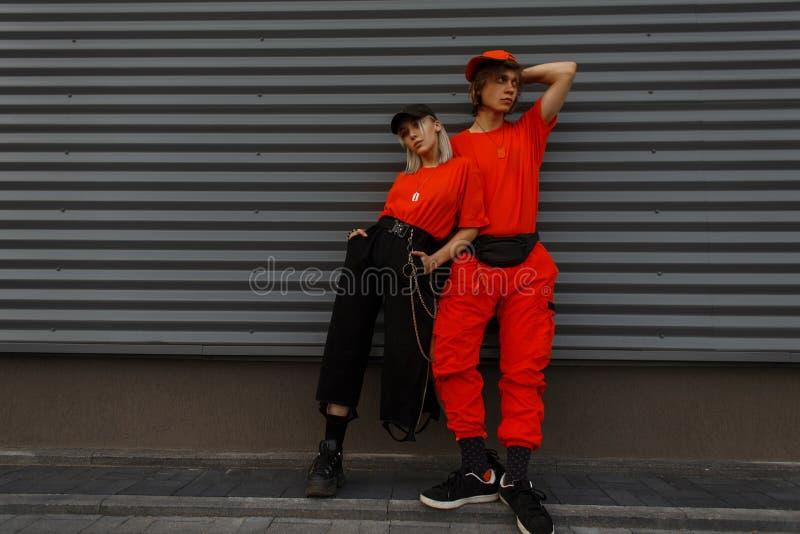 Junges schönes stilvolles Paar modelliert in Mode Kappen stockfotografie