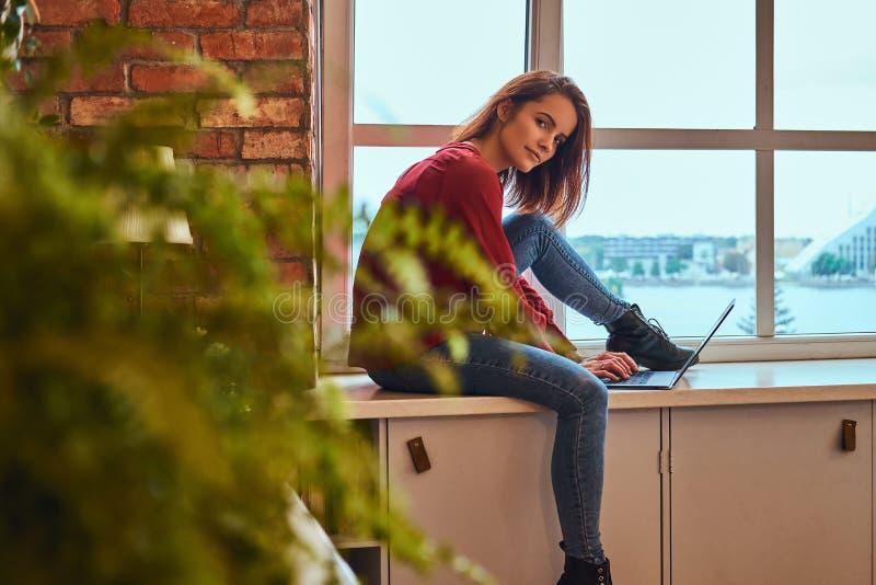 Junges schönes Studentenmädchen, das mit Laptop auf Fensterbrett im Studentenschlafsaal sitzt lizenzfreies stockfoto