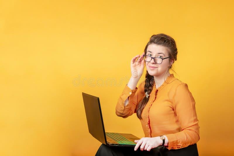 Junges, schönes und intelligentes Mädchen in den Gläsern arbeitet hinter einem Laptop, auf einem gelben Hintergrund im Studio stockbild