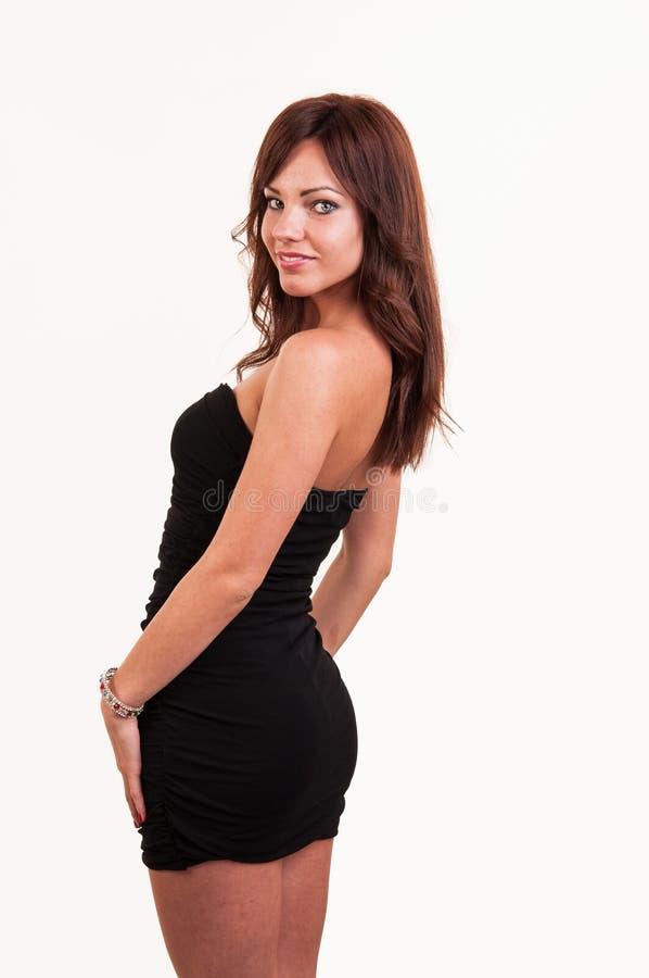 Junges schönes weibliches Modell im schwarzen Kleiderblick über ihr sollte stockfotografie