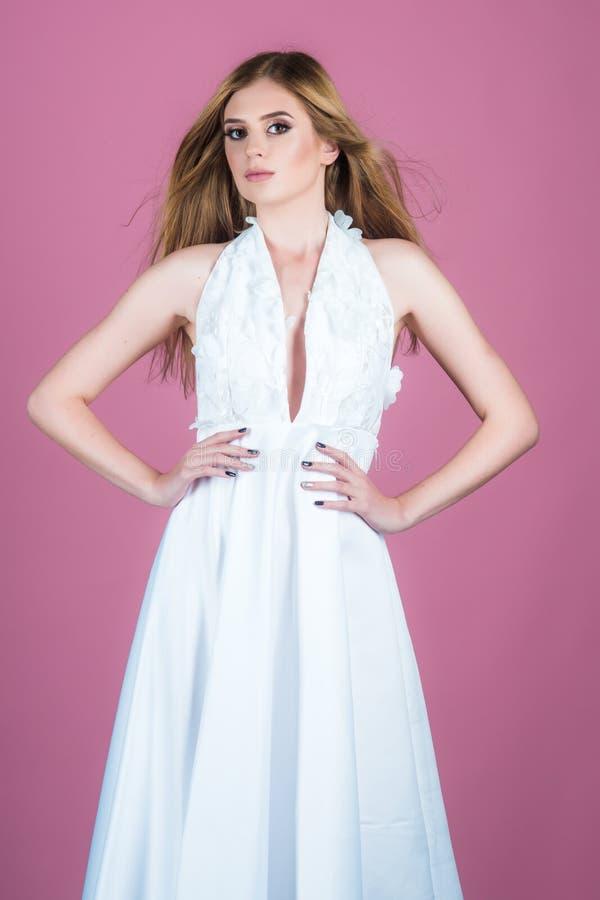 Junges schönes weibliches Modell im weißen Kleid auf rosa Hintergrund Studiofrau mit dem Brunettehaar und -make-up Kleidung stockfotografie