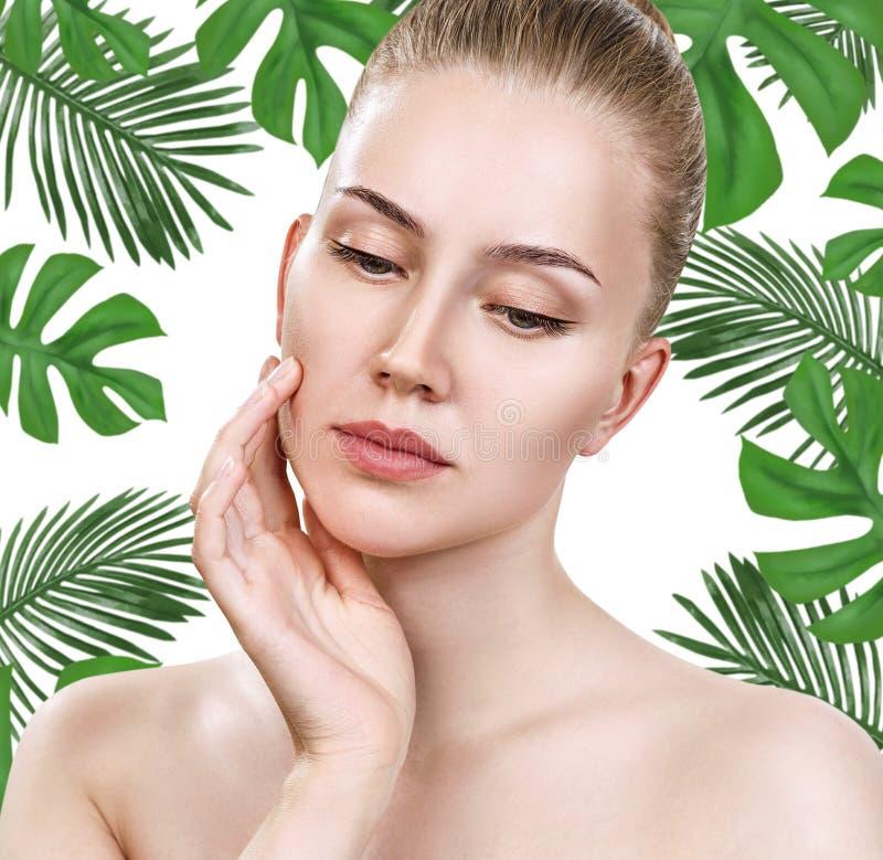 Junges Schönheitsgesicht unter grünen Palmblättern stockfotos